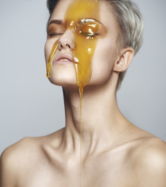 Beautiful woman with a honey on her face